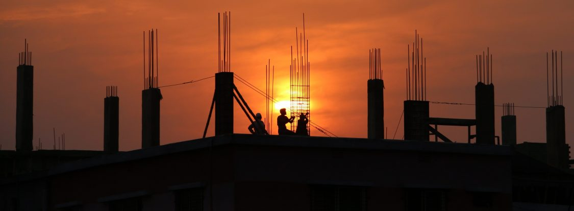 three construction workers on top of an unfinished roof at sunset